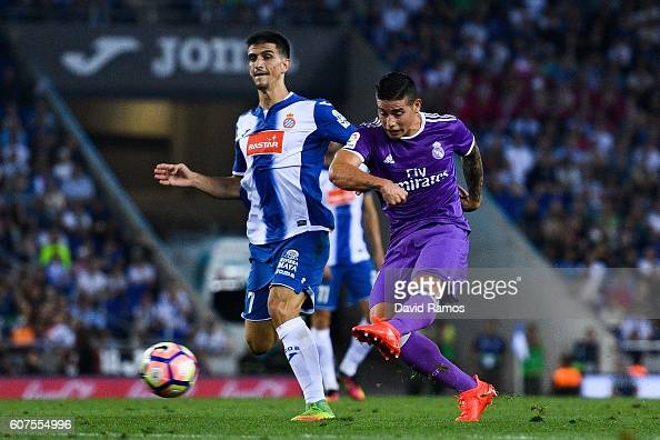 James Rodriguez of Real Madrid CF scores his team's first goal under a challenge by Gerard Moreno of RCD Espanyol during the La Liga match between...