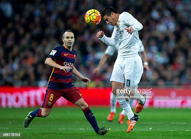 James Rodriguez of Real Madrid CF wins the header after Andres Iniesta of FC Barcelona during the La Liga match between Real Madrid CF and FC...