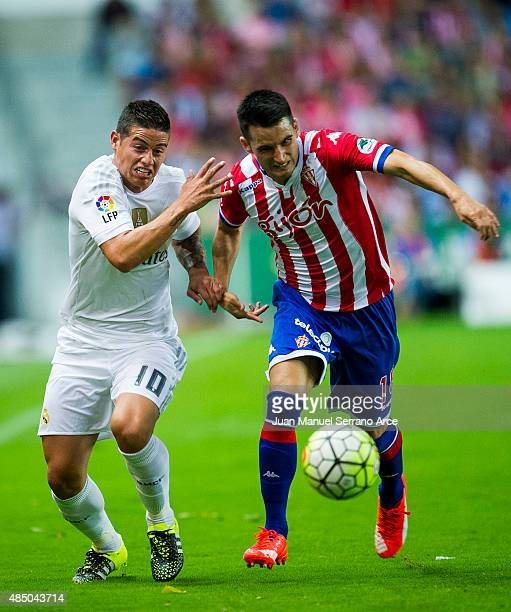 James Rodriguez of Real Madrid duels for the ball with Ismael Lopez of Real Sporting de Gijon during the La Liga match between Sporting Gijon and...