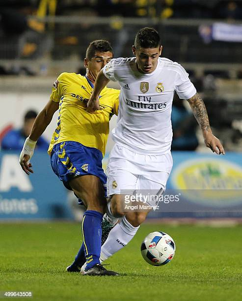 James Rodriguez of Real Madrid is tackled by Jon Ander Garrido of Cadiz during the Copa del Rey round of 32 first leg match between Cadiz and Real...