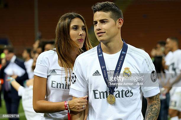 James Rodriguez of Real Madrid poses with his winners medal and wife Daniela Ospina following his team's victory in a penalty shootout during the...