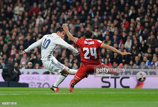 James Rodriguez of Real Madrid shoots past Gabriel Mercado of Sevilla FC to score Real's opening goal during the Copa del Rey Round of 16 First Leg...