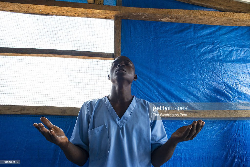 James S. Momoh, a health worker, prays during devotional at Bong County Ebola Treatment Unit, on Tuesday September 16, 2014.The newly opened 50 bed unit is managed by International Medical Corp, and was built by Save the Children. On its second day of operation to it has 3 new patients; one patient died Monday night.