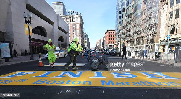 James Sawler left watches as Eric House puts down a straight black border Workers with Road Safe Traffic Systems paint the Boston Marathon Finish...