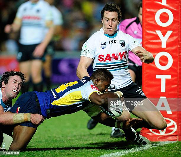 James Segeyaro of the Cowboys scores a try past Trent Waterhouse and David Simmons of the Panthers during the round 21 NRL match between the North...