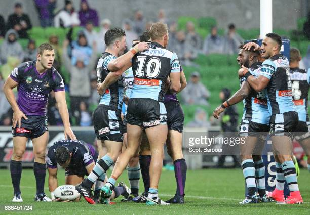 James Segeyaro of the Sharks is congratulated by his teammates after scoring the matchwinning try as Cameron Smith of the Melbourne Storm looks on...
