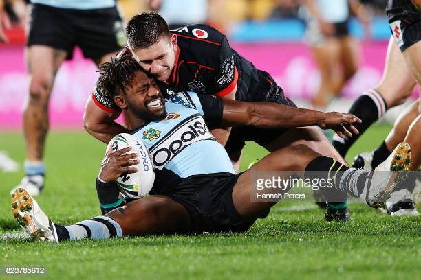 James Segeyaro of the Sharks is crushed by Jacob Lillyman of the Warriors during the round 21 NRL match between the New Zealand Warriors and the...