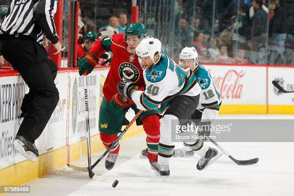 James Sheppard of the Minnesota Wild and Kent Huskins of the San Jose Sharks skate to the puck during the game at the Xcel Energy Center on March 23...