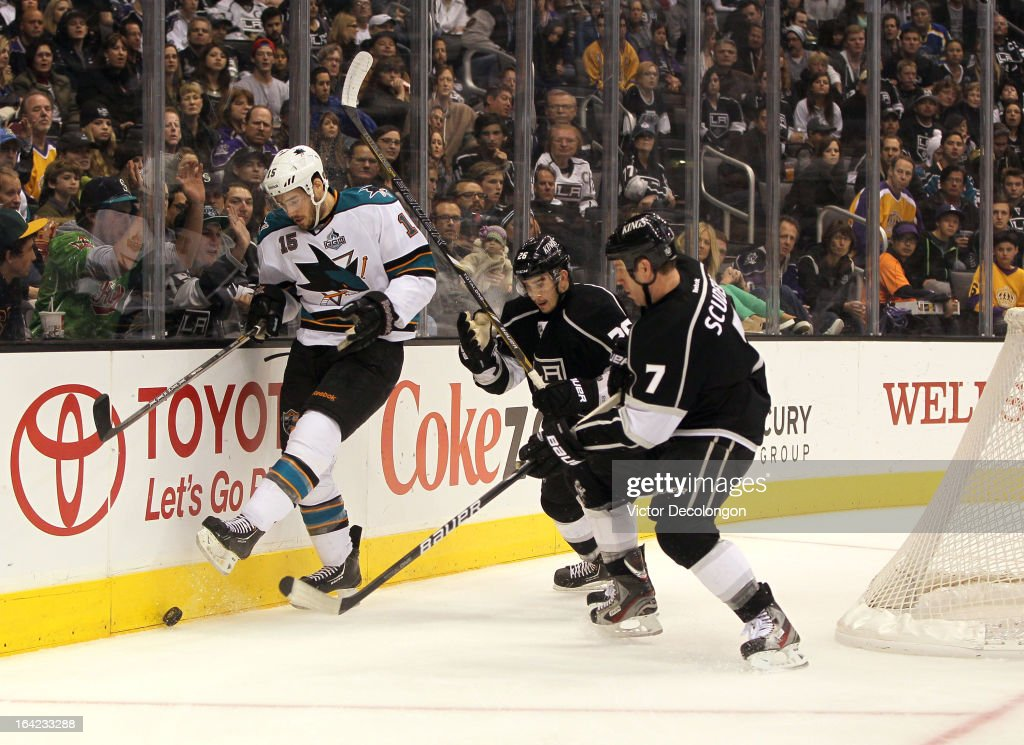 James Sheppard #15 of the San Jose Sharks kicks the puck along the end boards as Slava Voynov #26 and Rob Scuderi #7 of the Los Angeles Kings defend the play during the NHL game at Staples Center on March 16, 2013 in Los Angeles, California. The Kings defeated the Sharks 5-2.