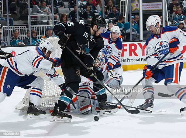 James Sheppard of the San Jose Sharks tries to score against Ben Scrives and Justin Schultz of the Edmonton Oilers during an NHL game on December 18...