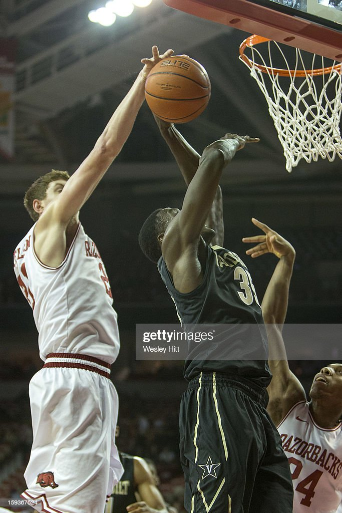 James Siakam #35 of the Vanderbilt Commodores is blocked from behind by Hunter Mickelson #21 of the Arkansas Razorbacks at Bud Walton Arena on January12, 2013 in Fayetteville, Arkansas. The Razorbacks defeated the Commodores 56-33.