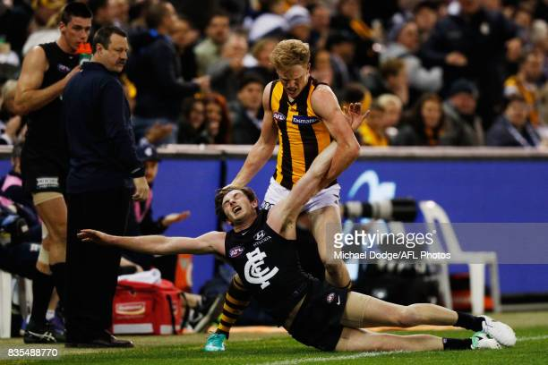 James Sicily of the Hawks wrestles Jed Lamb of the Blues to the ground behind play during the round 22 AFL match between the Carlton Blues and the...