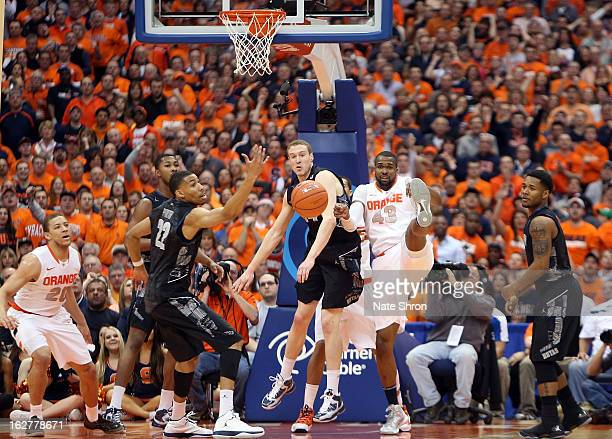 James Southerland of the Syracuse Orange falls backwards as he reaches for the rebound against Nate Lubick and Otto Porter Jr #22 of the Georgetown...