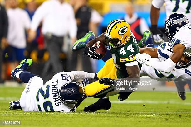 James Starks of the Green Bay Packers gets tackled by Earl Thomas of the Seattle Seahawks in the first quarter against the Seattle Seahawks during...