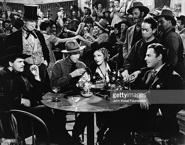 James Stewart and Marlene Dietrich share a drink with Brian Donlevy and friends in a scene from the film 'Destry Rides Again' directed by George...