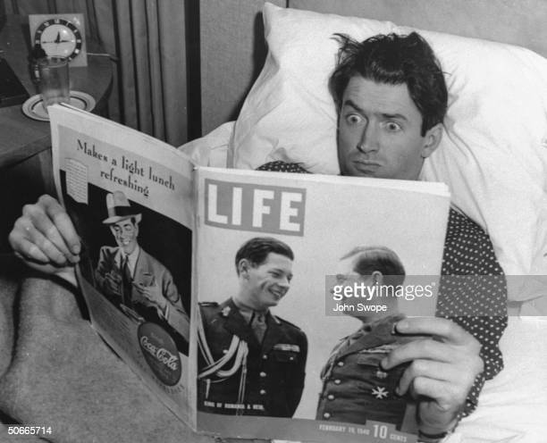 James Stewart in bed looking at Life Magazine