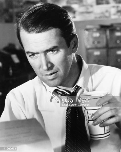 James Stewart US actor looking serious reading a document while holding a paper cup in a publicity still issued for the film 'Mr Smith Goes to...