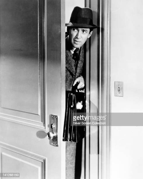 James Stewart US actor wearing a fedora and an overcoat carrying a briefcase appearing through a door which is ajar in a publicity still issued for...