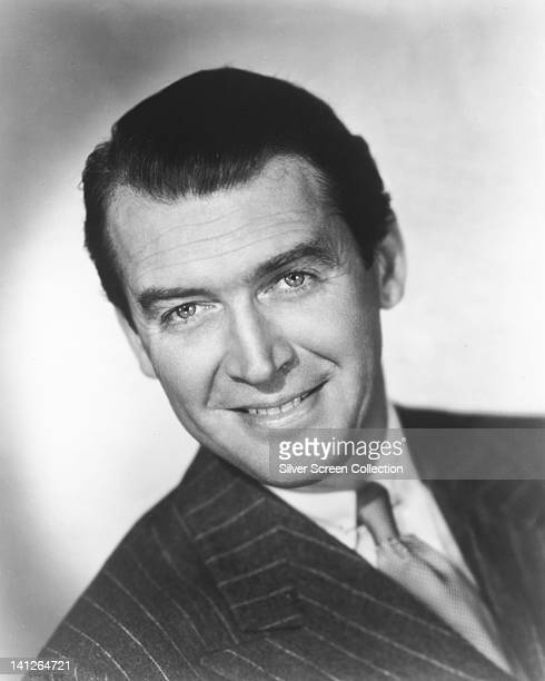 James Stewart US actor wearing a pin stripe suit smiling in a studio portrait against a white background circa 1950
