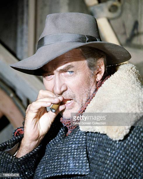 James Stewart US actor wearing widebrimmed hat and a jacket with a fur collar as he smokes a cigar in an image issued as publicity for the film...