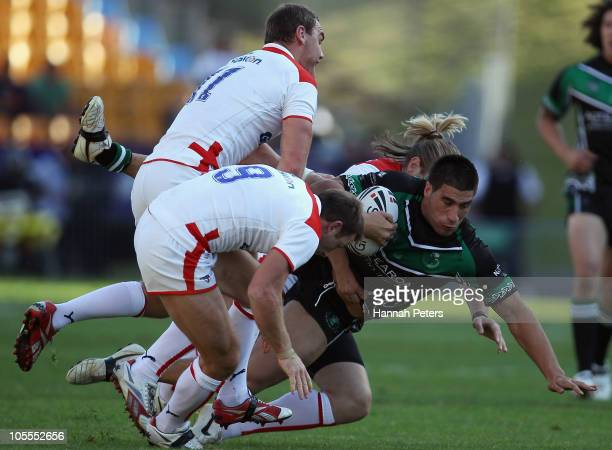 James Tamou of New Zealand Maori is brought down by James Roby Gareth Ellis and Erol Crabtree of England during the international match between New...
