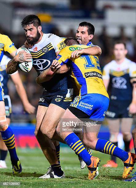 James Tamou of the Cowboys is tackled by Will Hopoate and Isaac De Gois of the Eels during the round 20 NRL match between the North Queensland...