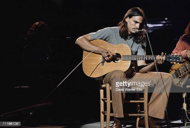 James Taylor US singersongwriter playing the guitar while sitting on a chair during a concert circa 1970