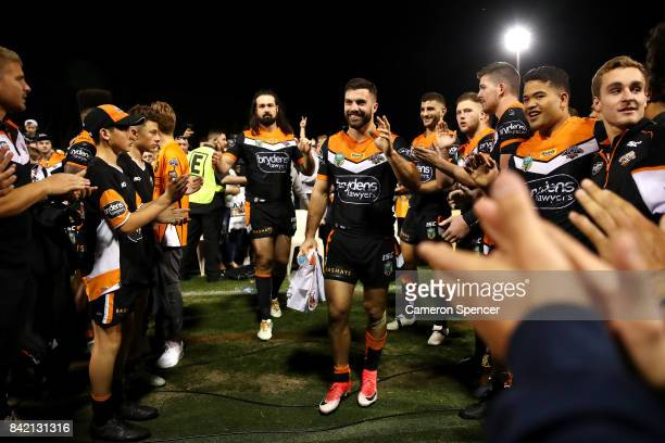 James Tedesco and Aaron Woods of the Tigers are applauded off the field after playing their final game for the Tigers during the round 26 NRL match...