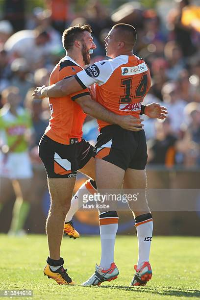 James Tedesco and Kyle Lovett of the Tigers celebrate Lovett scoring a try during the round one NRL match between the Wests Tigers and the New...