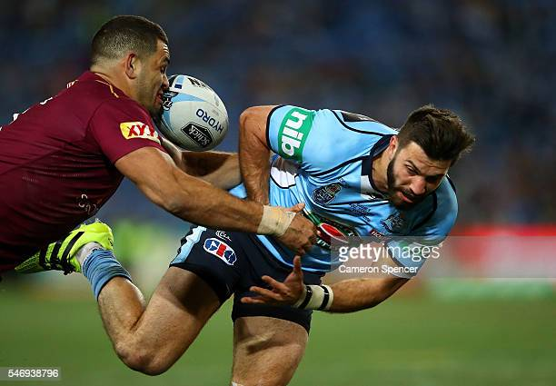 James Tedesco of the Blues loses the ball in the tackle by Greg Inglis of the Maroons during game three of the State Of Origin series between the New...