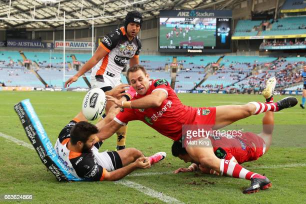 James Tedesco of the Tigers drops the ball over the line as Jason Nightingale of the Dragons defends during the round five NRL match between the...