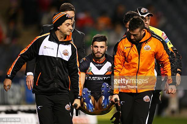 James Tedesco of the Tigers is carried from the field after sustaining an injury in the opening minutes during the round 16 NRL match between the...