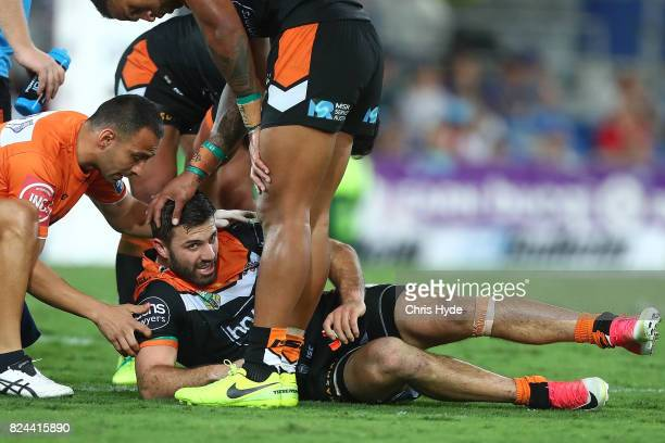 James Tedesco of the Tigers is helped during the round 21 NRL match between the Gold Coast Titans and the Wests Tigers at Cbus Super Stadium on July...