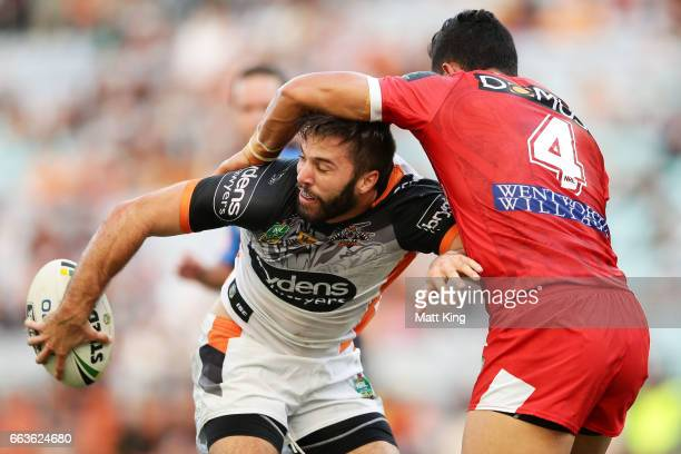James Tedesco of the Tigers offloads the ball in a tackle during the round five NRL match between the Wests Tigers and the St George Illawarra...