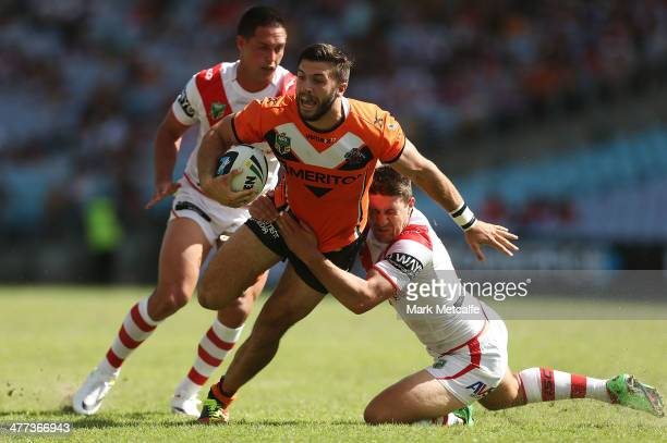 James Tedesco of the Wests Tigers is tackled by Gareth Widdop of the Dragons during the round one NRL match between the St George Illawarra Dragons...