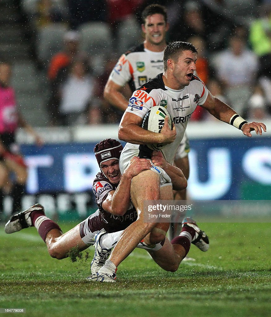 James Tedesco of the Wests Tigers is tackled by the Manly defence during the round four NRL match between the Manly Sea Eagles and the Wests Tigers at Bluetongue Stadium on March 28, 2013 in Gosford, Australia.