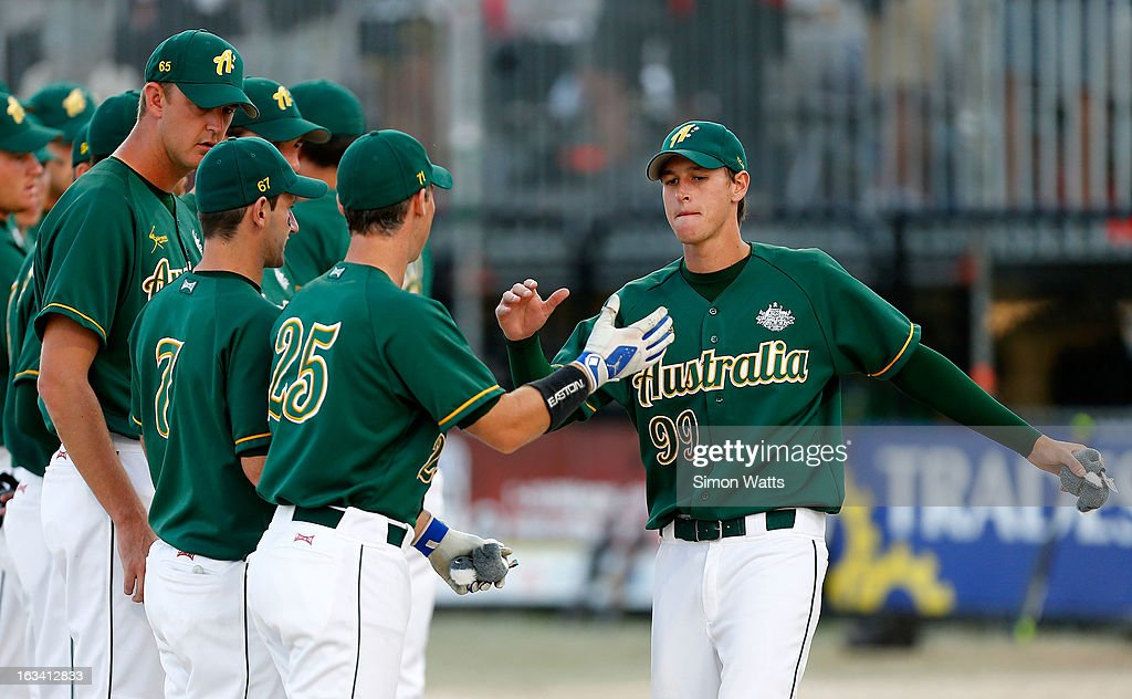 James Todhunter of Australia high-fives team mates during the playoff match between Australia and Argentina at Tradstaff Sports Stadium on March 9, 2013 in Auckland, New Zealand.