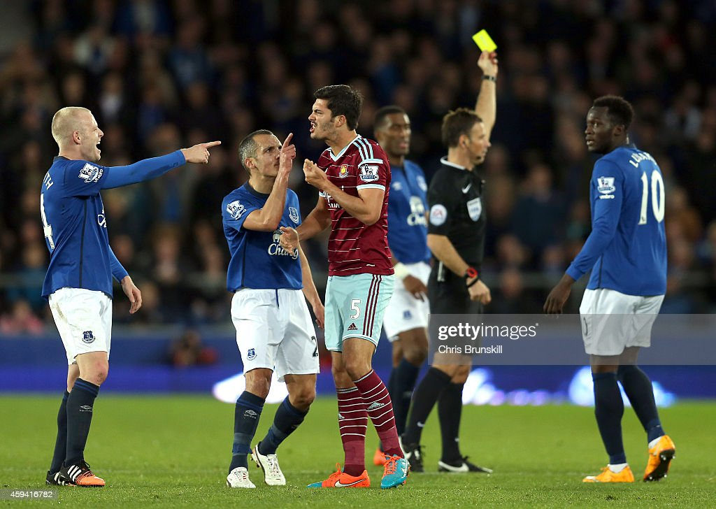 James Tomkins of West Ham United is challenged by Steven Naismith and Leon Osman of Everton after he clashed with team-mate Kevin Mirallas during the Barclays Premier League match between Everton and West Ham United at Goodison Park on November 22, 2014 in Liverpool, England.