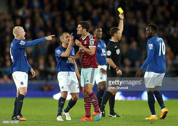 James Tomkins of West Ham United is challenged by Steven Naismith and Leon Osman of Everton after he clashed with teammate Kevin Mirallas during the...