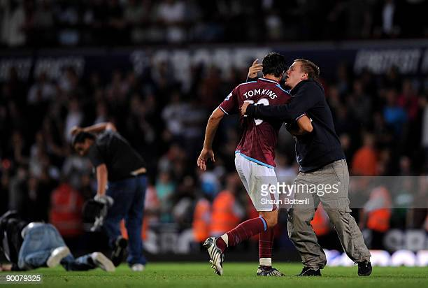 James Tomkins of West Ham United is grabbed by a fan during the Carling Cup second round match between West Ham United and Millwall at Upton Park on...