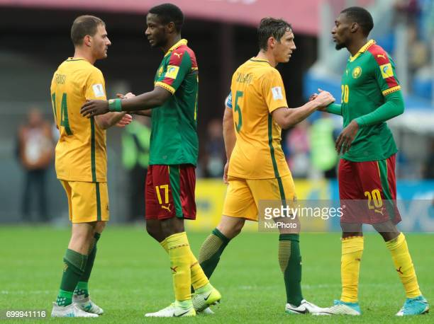 James Troisi Mark Milligan of the Australia national football team and Arnaud Djoum Karl Toko Ekambi of the Cameroon national football team after the...