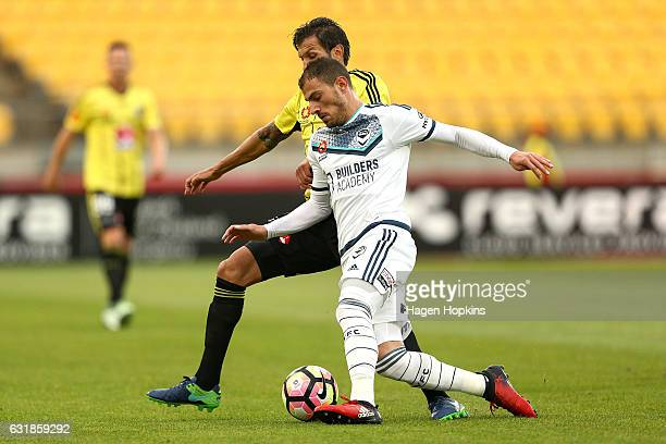 James Troisi of Melbourne Victory holds off the defence of Vince Lia of the Phoenix during the round seven ALeague match between the Wellington...