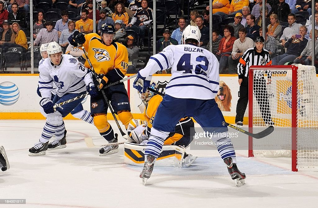 James van Riemsdyk #21 and <a gi-track='captionPersonalityLinkClicked' href=/galleries/search?phrase=Tyler+Bozak&family=editorial&specificpeople=6183313 ng-click='$event.stopPropagation()'>Tyler Bozak</a> #42 of the Toronto Maple Leafs fight Mattias Ekholm #42 of the Nashville Predators for position in front of Predators goalie <a gi-track='captionPersonalityLinkClicked' href=/galleries/search?phrase=Pekka+Rinne&family=editorial&specificpeople=2118342 ng-click='$event.stopPropagation()'>Pekka Rinne</a> #35 at Bridgestone Arena on October 10, 2013 in Nashville, Tennessee.