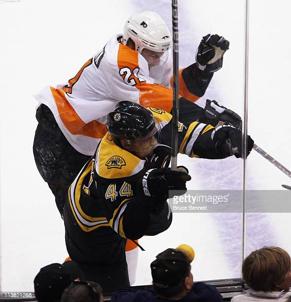 James van Riemsdyk of the Philadelphia Flyers hits Dennis Seidenberg of the Boston Bruins into the glass in Game Four of the Eastern Conference...