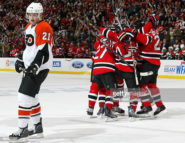 James van Riemsdyk of the Philadelphia Flyers looks away as the New Jersey Devils celebrate the game winning goal late in the third period in Game...