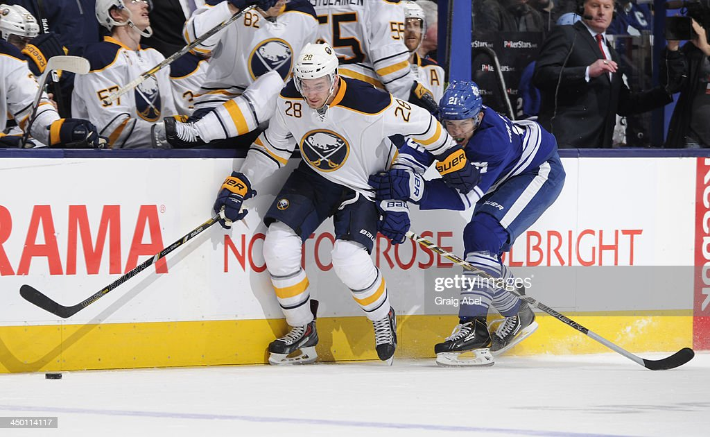 James van Riemsdyk #21 of the Toronto Maple Leafs battles for the puck with <a gi-track='captionPersonalityLinkClicked' href=/galleries/search?phrase=Zemgus+Girgensons&family=editorial&specificpeople=8050732 ng-click='$event.stopPropagation()'>Zemgus Girgensons</a> #28 of the Buffalo Sabres during NHL game action November 16, 2013 at the Air Canada Centre in Toronto, Ontario, Canada.