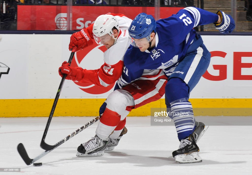 James van Riemsdyk #21 of the Toronto Maple Leafs battles for the puck with Tomas Tatar #21 of the Detroit Red Wings during NHL game action March 29, 2014 at the Air Canada Centre in Toronto, Ontario, Canada.