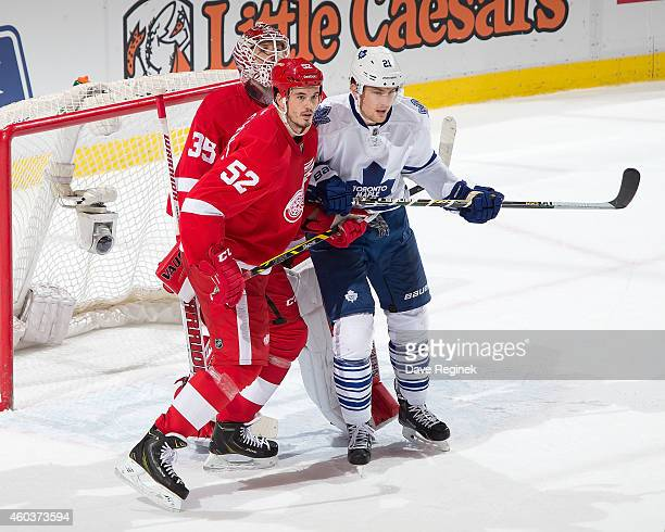 James van Riemsdyk of the Toronto Maple Leafs battles in front with Jonathan Ericsson of the Detroit Red Wings as Jimmy Howard of the Wings follows...
