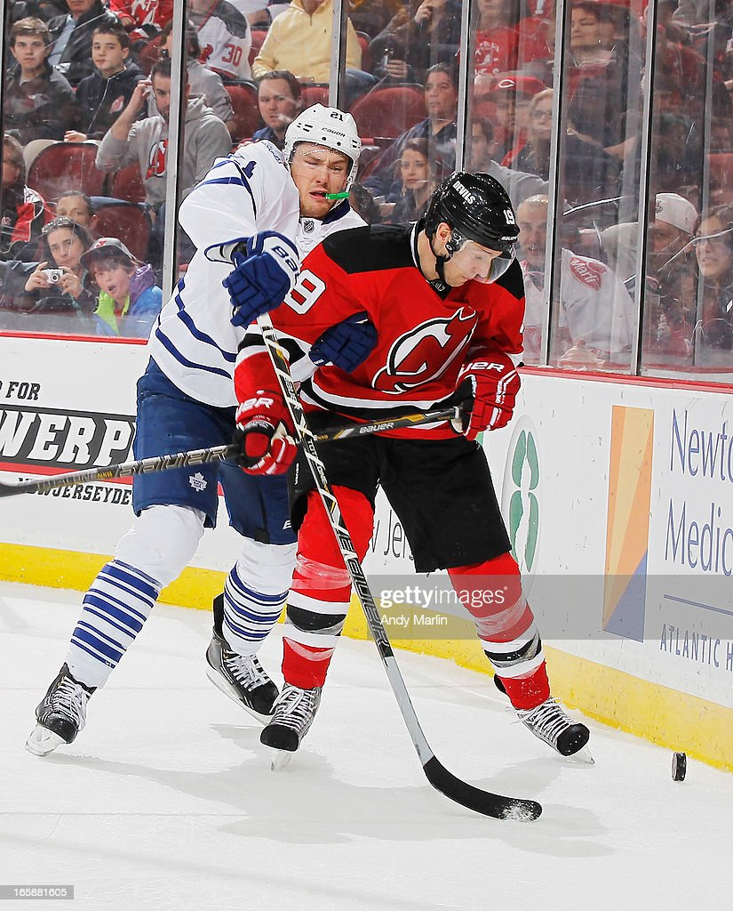 James van Riemsdyk #21 of the Toronto Maple Leafs checks and Travis Zajac #19 of the New Jersey Devils battle for a loose puck during the game at the Prudential Center on April 6, 2013 in Newark, New Jersey.