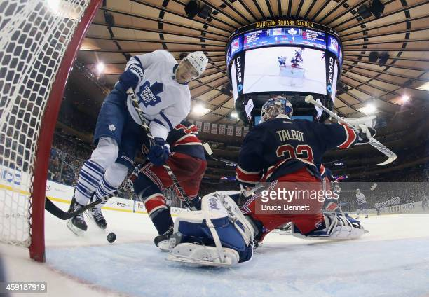 James van Riemsdyk of the Toronto Maple Leafs gets tripped up in front of Cam Talbot of the New York Rangers at Madison Square Garden on December 23...